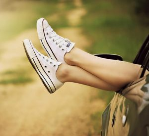 Legs sticking out of car window (loosely crossed with casual shoes)