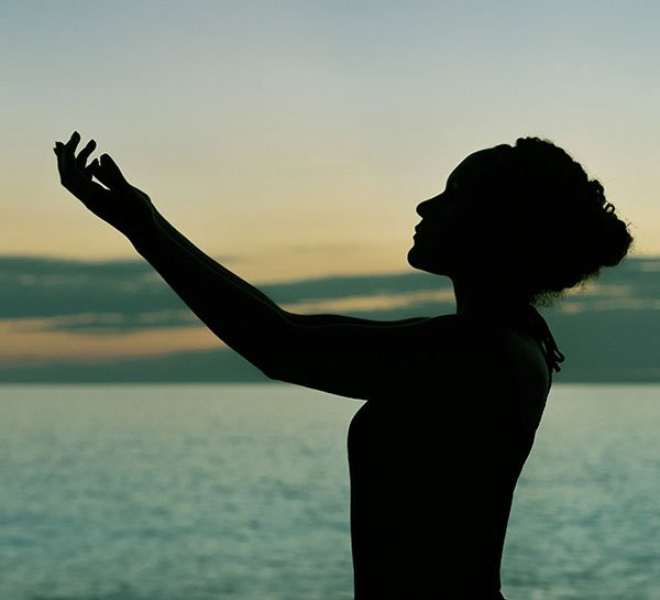 Silhouette of a woman standing sideways and lifting her hands and arms