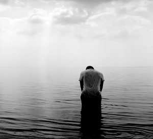 Black and white photo of a man with head bowed standing in ocean