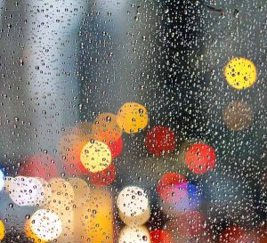 Rain on window with coloured lights in the background