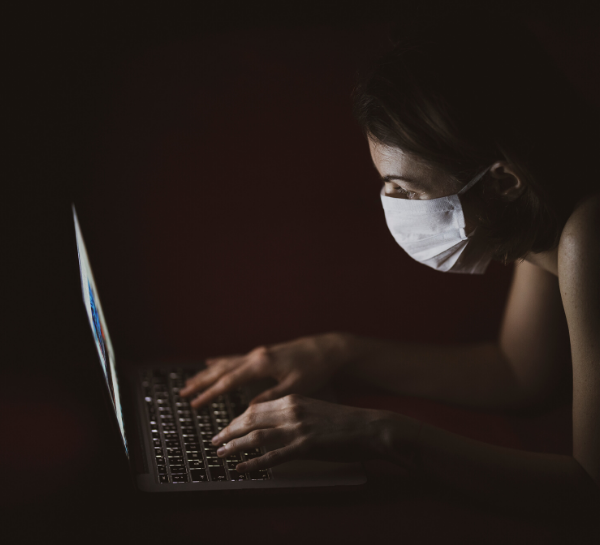 Woman wearing mask and typing at laptop