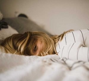 woman lying down on bed with hair covering face