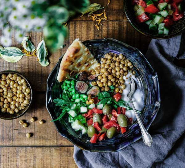 A plate of healthy food including chick peas, peppers and greens